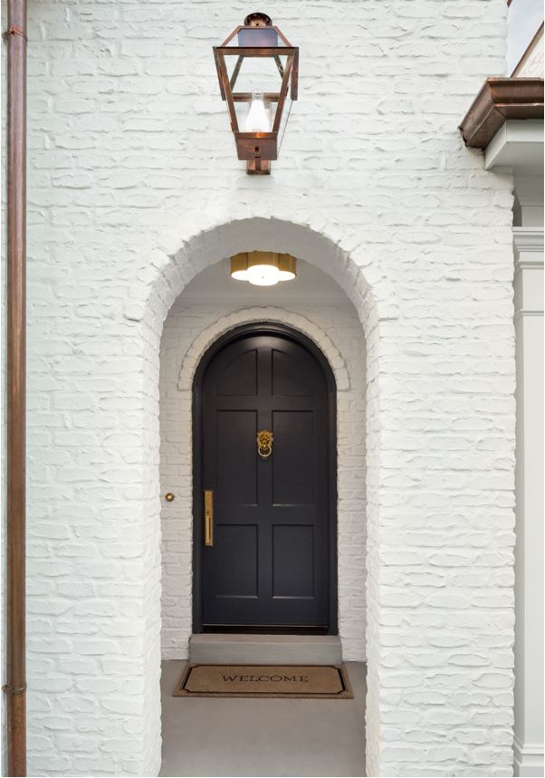 A white painted brick Tudor house with arched doorways, black front door, and copper downspouts.