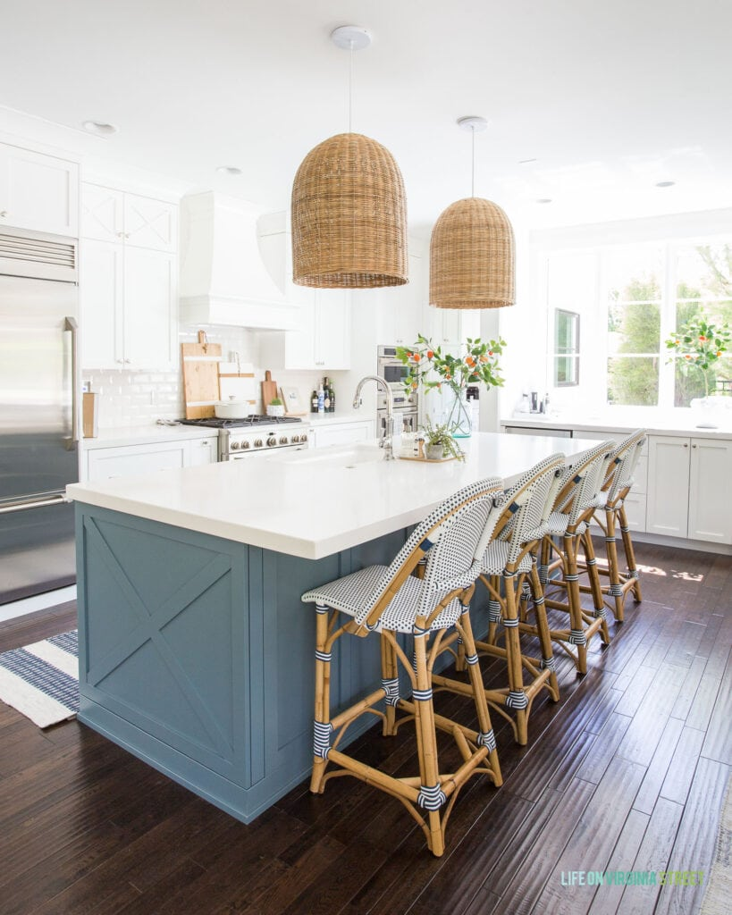 A kitchen with Benjamin Moore Simply White cabinets, Providence Blue island, woven basket pendant lights, bistro counter stools, a striped rug and faux orange stems.