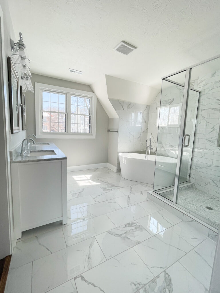 Master bathroom with affordable ceramic tile that looks like Carrara marble! Includes a soaking tub, glass vanity lights, multiple windows, large glass framed shower, and white double vanity.