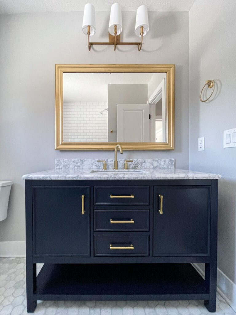 Navy blue vanity with gold hardware and marble hex flooring.