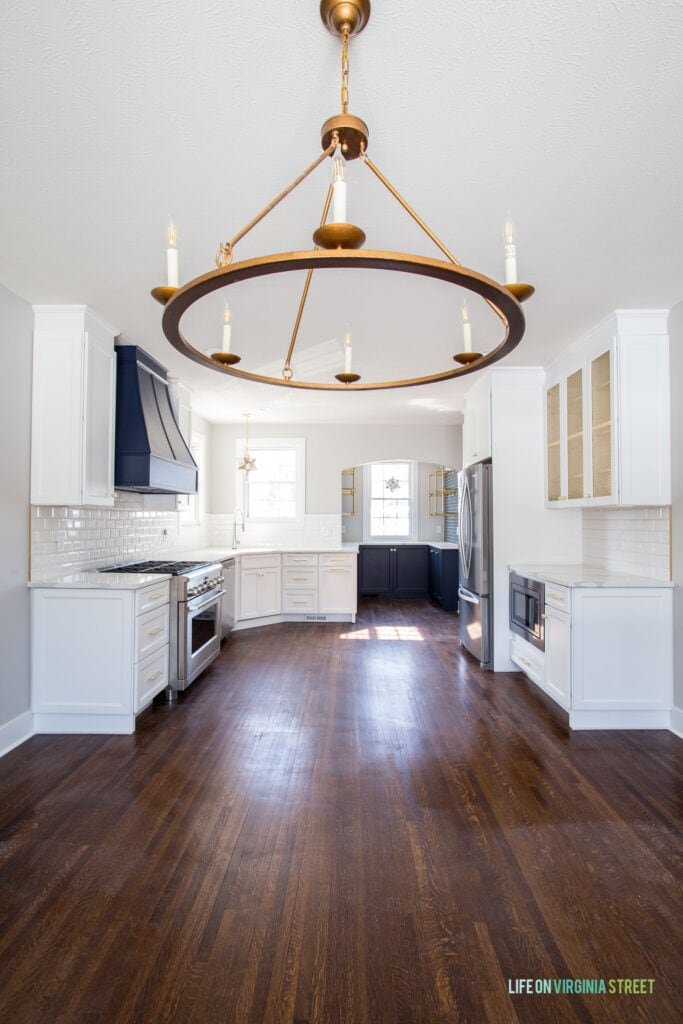 Tudor house renovation with dark hardwood floors, white kitchen cabinets, Sherwin Williams Naval range hood and lower kitchen cabinets, and a large wagon wheel light fixture.