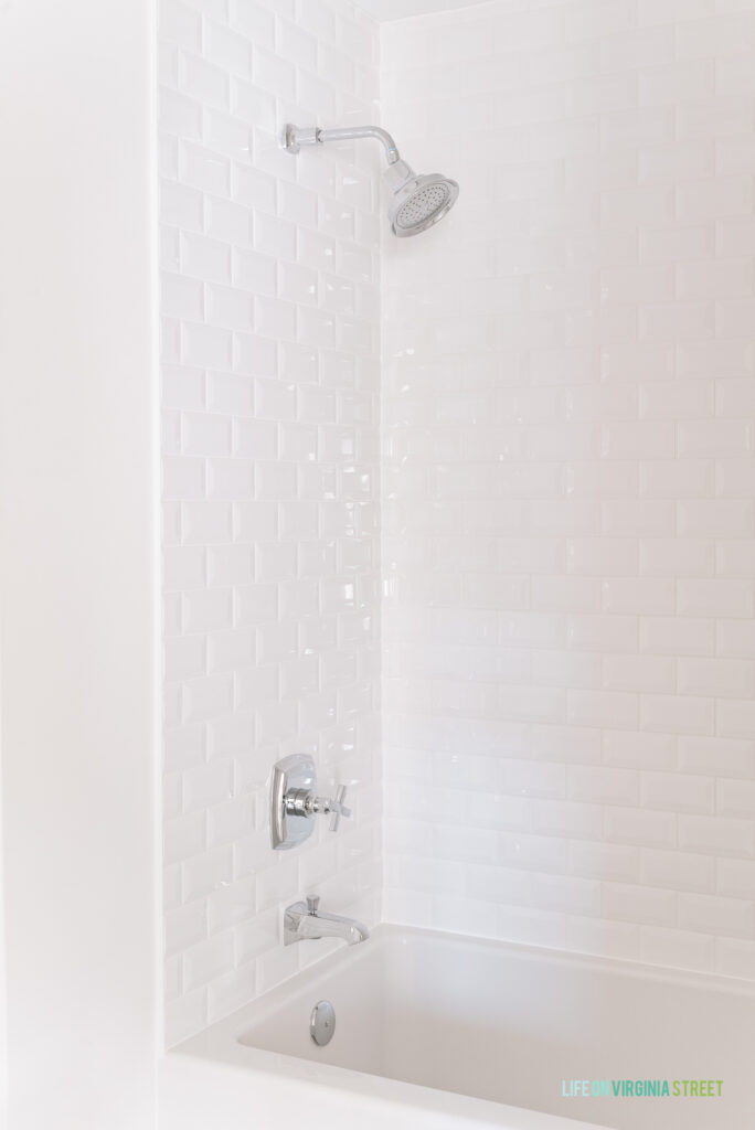 A remodeled shower tiled with white beveled subway tile and silver cross bath fixtures.