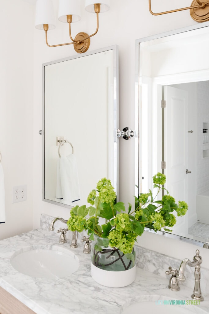 A Jack & Jill bathroom remodel reveal with Carrara marble countertops, polished nickel pivot mirrors, gold light fixtures, polished nickel faucets and faux viburnum stems.