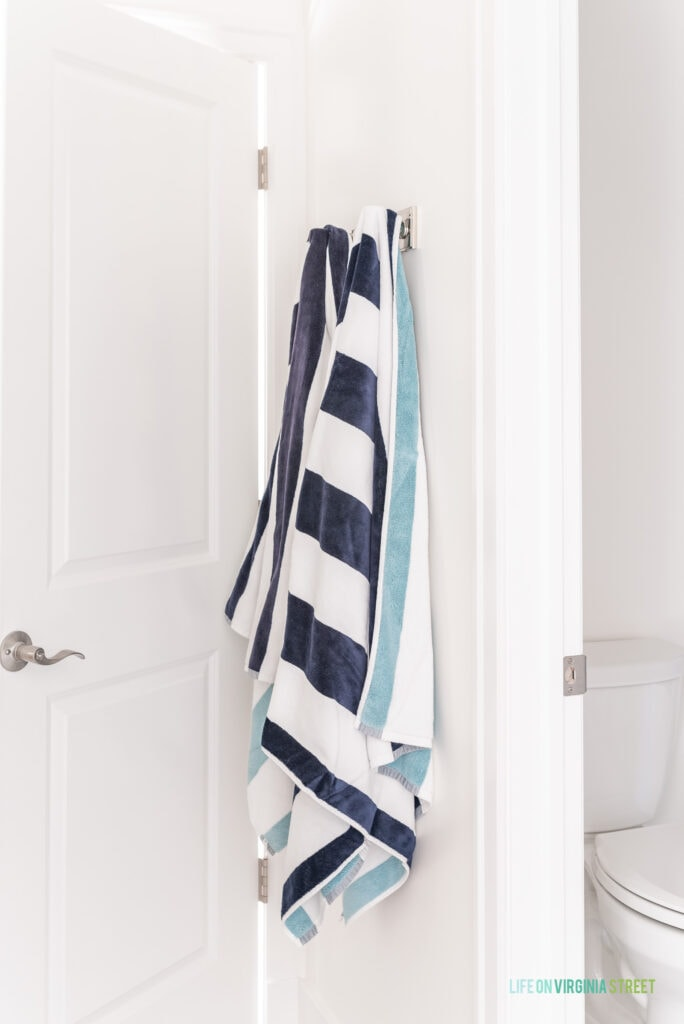Robe hooks used in a bathroom to hold reversible blue striped pool towels.