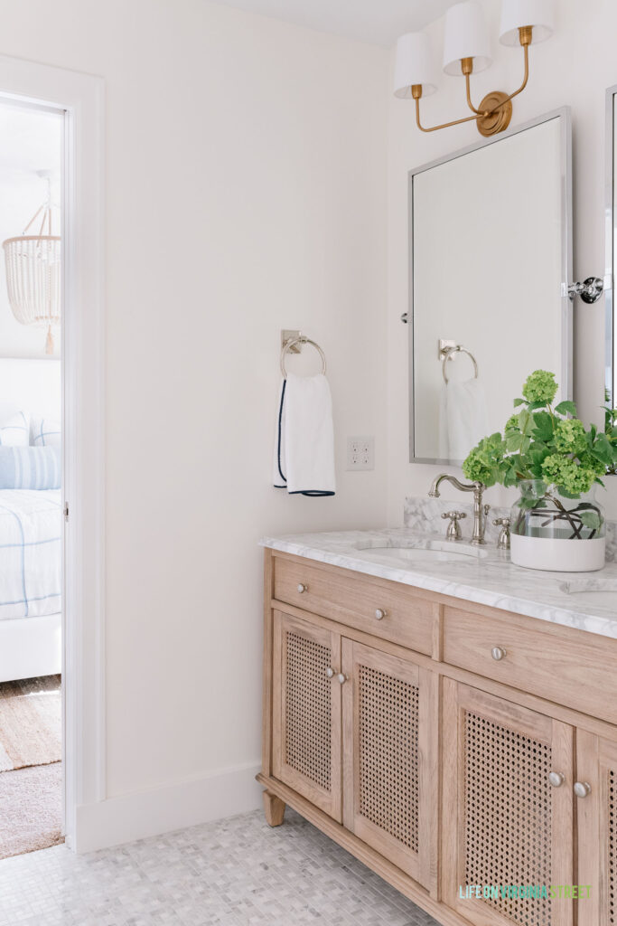 A Jack and Jill bathroom remodel that used wood cane vanity, Carrara marble floors, silver pivot mirrors, gold light fixtures and blue and green accents. You can see the bedroom in the background.