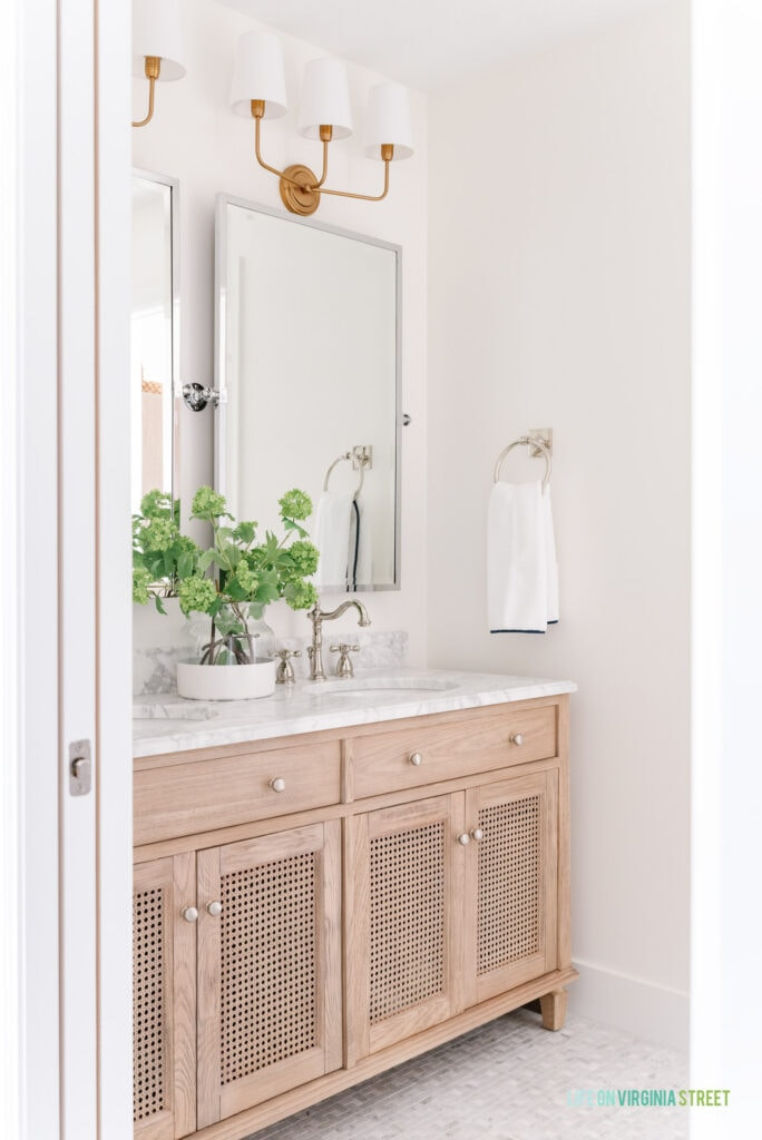 Jack & Jill Bathroom remodel reveal with Carrara marble pinwheel tile floors, a wood cane vanity, polished nickel pivot mirrors, and gold bathroom sconces.