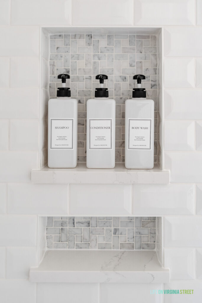 A bathroom shower niche with white beveled subway tiles, marble pinwheel tile, Silestone ledge shelf for shampoo bottles, and a lower niche to hold bar soap and razors.