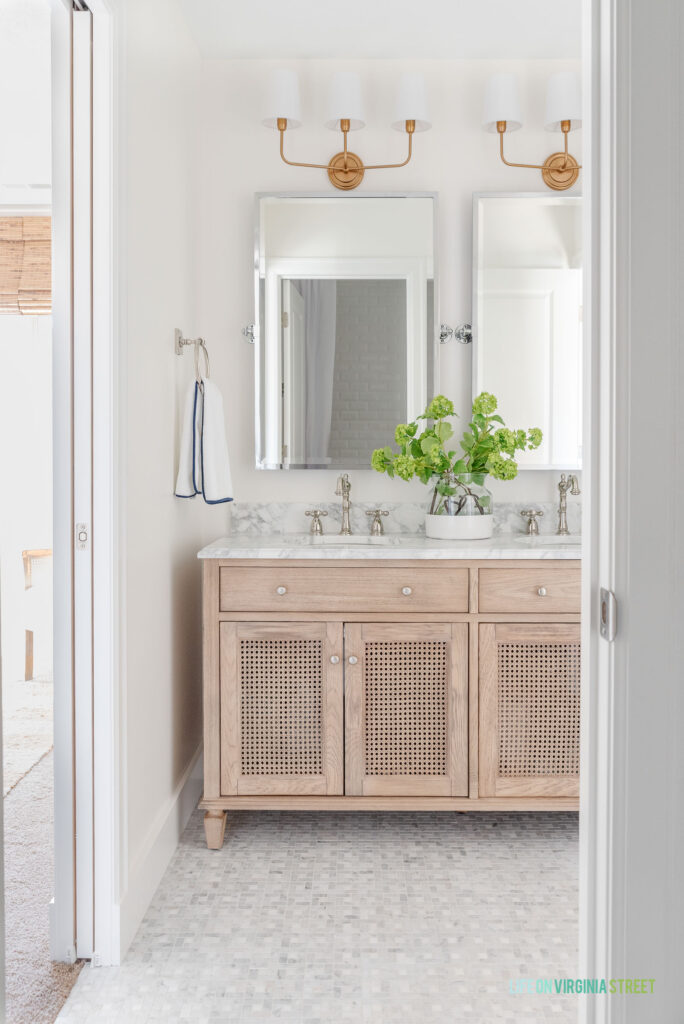 A Jack and Jill bathroom remodel with small marble tile floors, a wood & cane vanity, silver pivot mirrors, round towel rings, gold light fixtures, and white and navy blue towels.