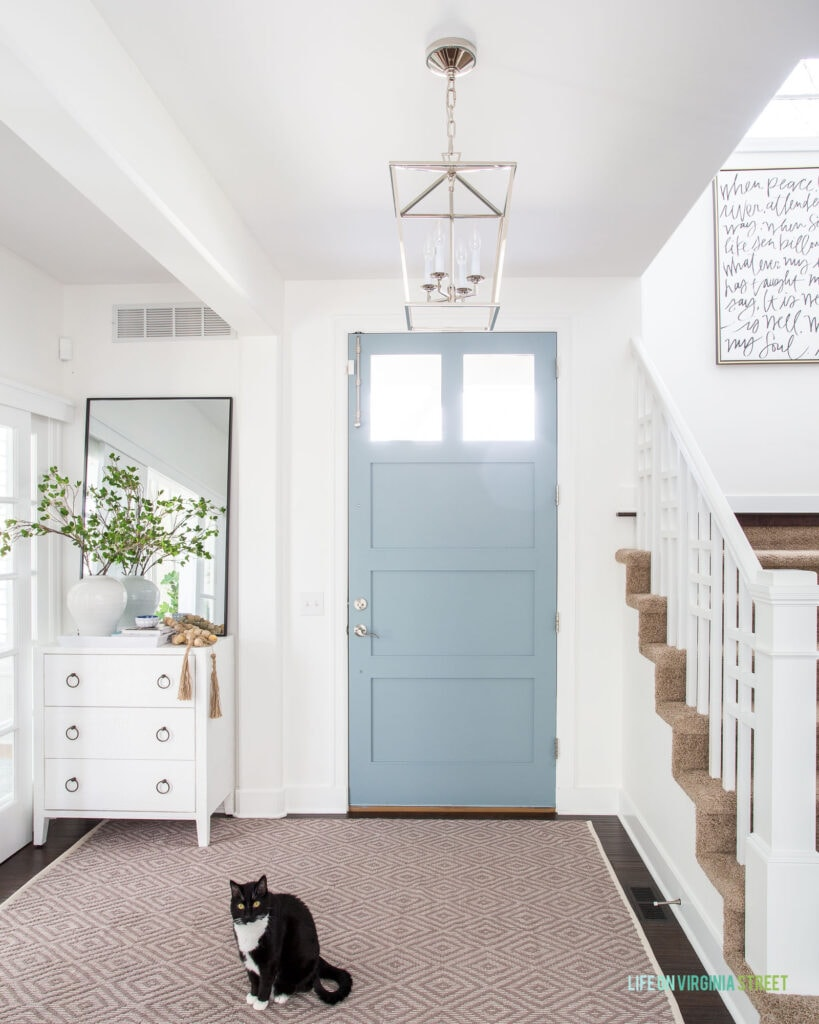 A light and bright entryway with a neutral rug in a diamond pattern, white cabinet, tall leaning mirror, blue front door, and a lantern pendant light.