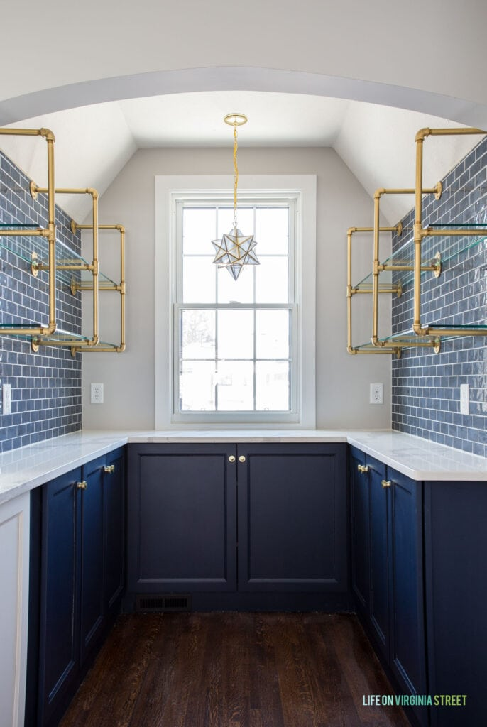 A kitchen butler's pantry with Sherwin Williams Naval cabinets, gold pipe & glass shelves, a Moravian star pendant light, and white quartz countertops.