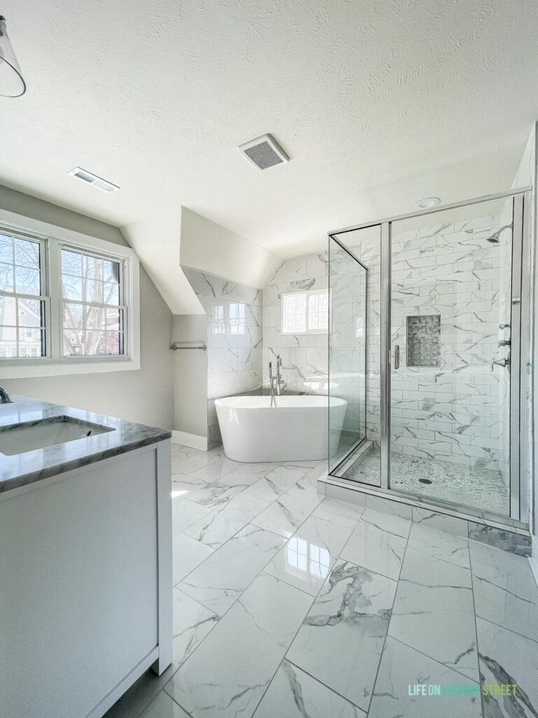 Master bathroom with affordable ceramic tile that looks like Carrara marble! Includes a soaking tub, large glass framed shower, and white double vanity.