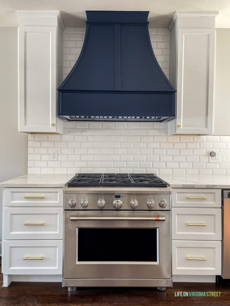 A kitchen range with Sherwin Williams Naval range hood, white kitchen cabinets, and white beveled subway tile.