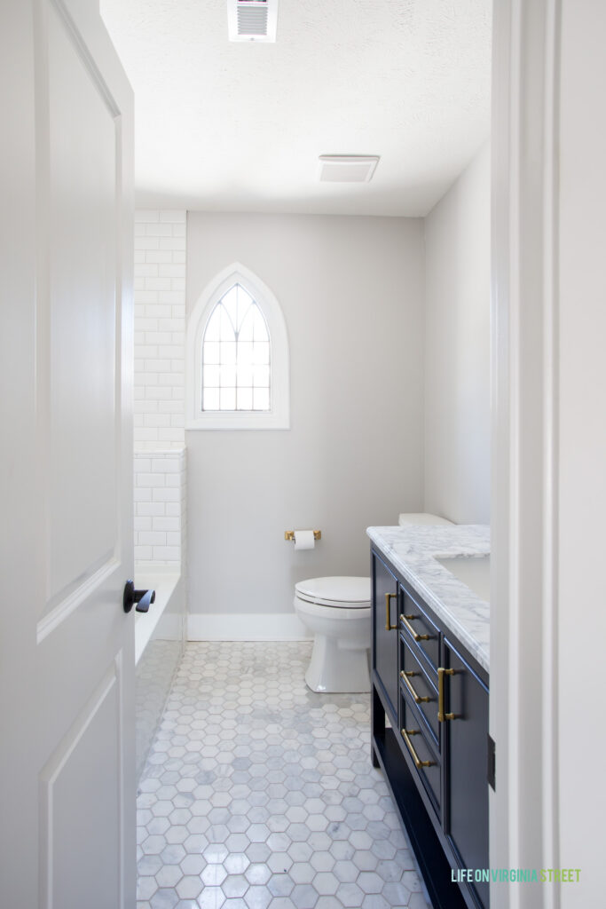 A hallway bathroom with marble hex floors, white beveled subway tile shower, navy blue vanity with Carrara marble top, original leaded pane arched window, and gold accents.