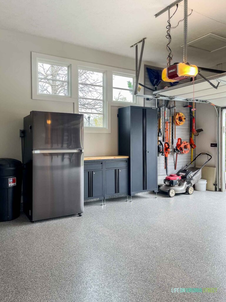 Garage workbench and and organized garage slat wall to store yard tools.