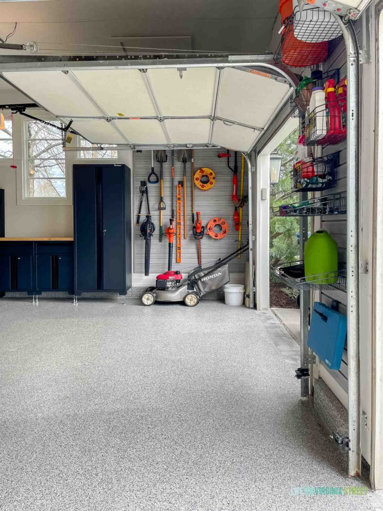 Garage organization with a slat wall, storage cabinets, polyaspartic floors, workbench and more!