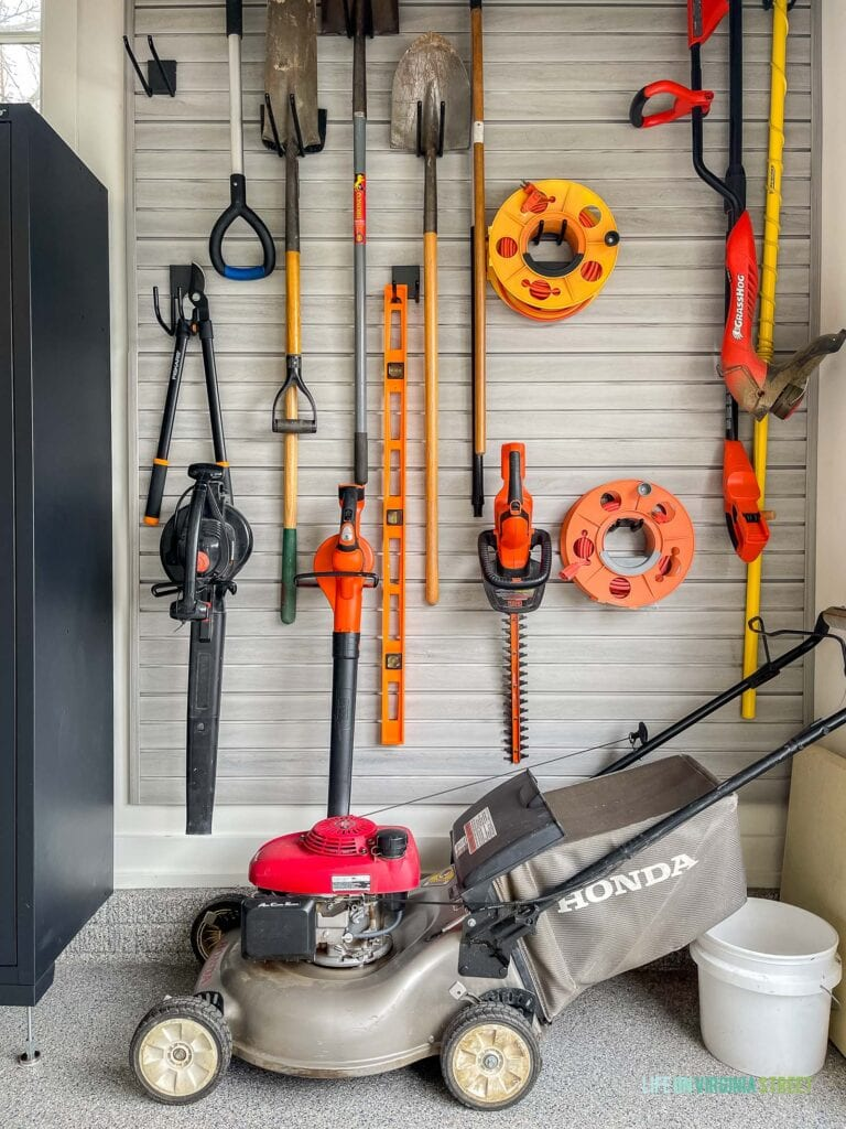 Gardening tools stored on a garage slat wall to keep the garage organized.