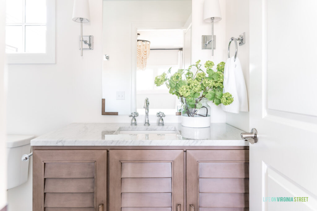 A wood shutter vanity cabinet in a small guest bathroom. Includes a Carrara marble countertop, chrome faucet, chrome sconce lights, and paint dipped vase filled with viburnum stems.