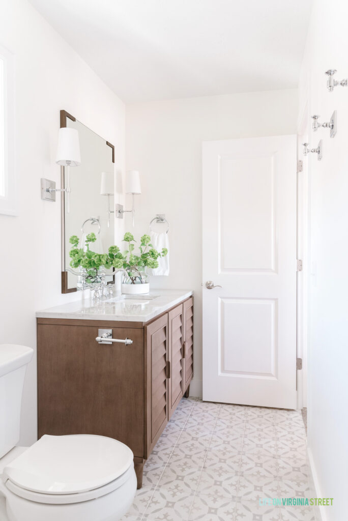A small guest bathroom remodel featuring a louvered wood vanity, neutral patterned tile floors, chrome sconce lights, a tall vertical mirror with bracket corners, and chrome robe hooks on the wall for towels.