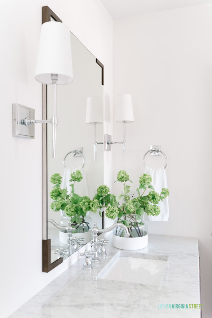 A Carrara marble bathroom countertop with faux viburnum stems, chrome sconce lights and a large vertical mirror.