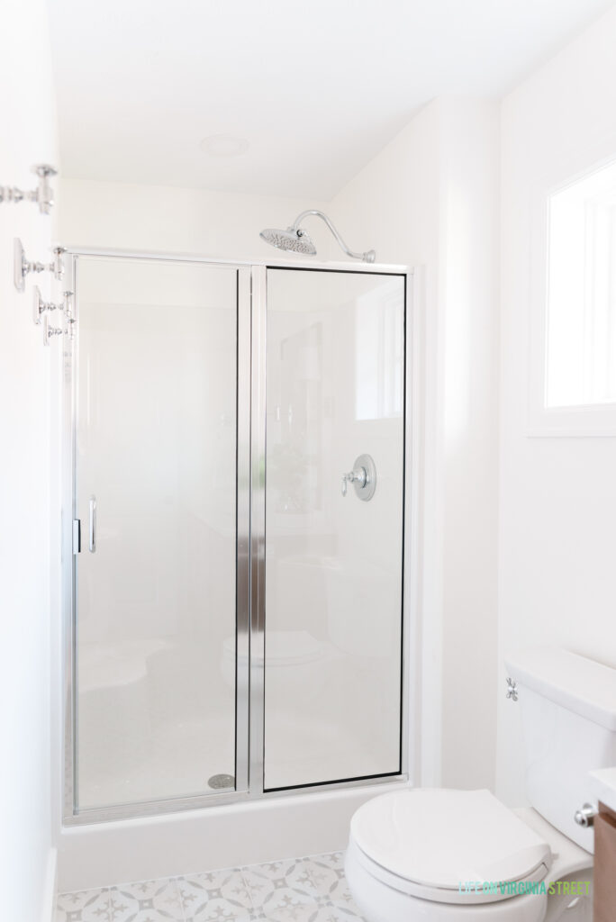 A chrome framed shower door in a shower insert. Also shown is a small square window, cement tile looking floors, robe hooks and a large shower head.