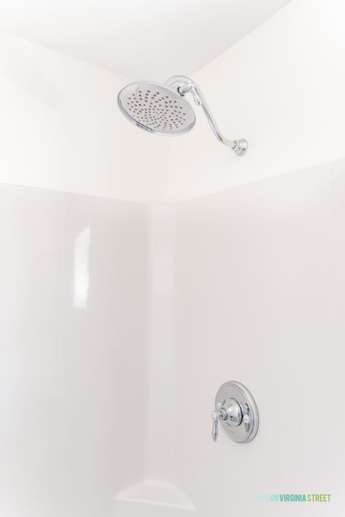 A large chrome shower head in a shower insert stall.