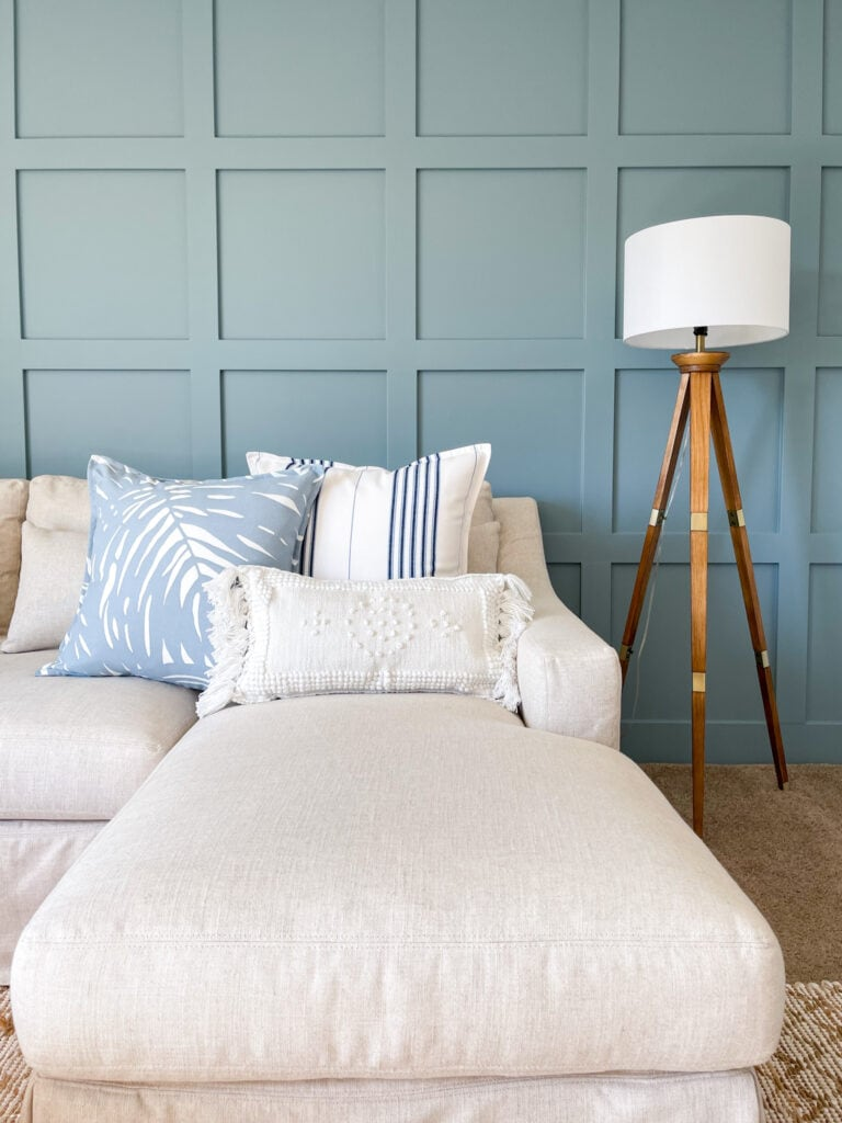 Serena & Lily summer pillows on a linen sectional with a blue board and batten wall and tripod floor lamp.