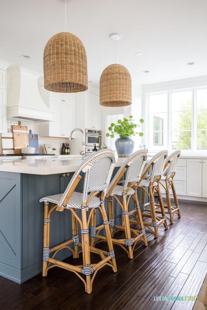 This Serena & Lily Riviera Counter Stool review includes photos of the stool in this coastal style kitchen with white cabinets, a blue island, dark hardwood floors and a large window.