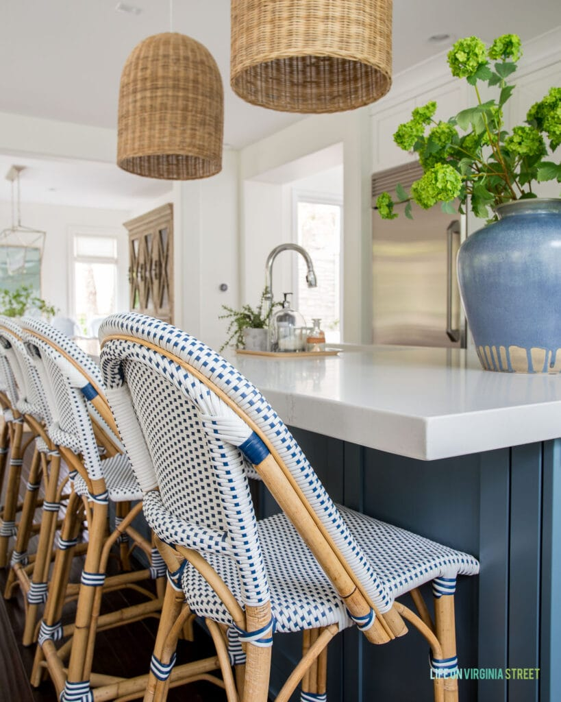 A row of Serena & Lily Riviera Counter Stools in a coastal inspired kitchen with blue island, white quartz countertops, and a large blue ceramic vase filled with faux viburnum.
