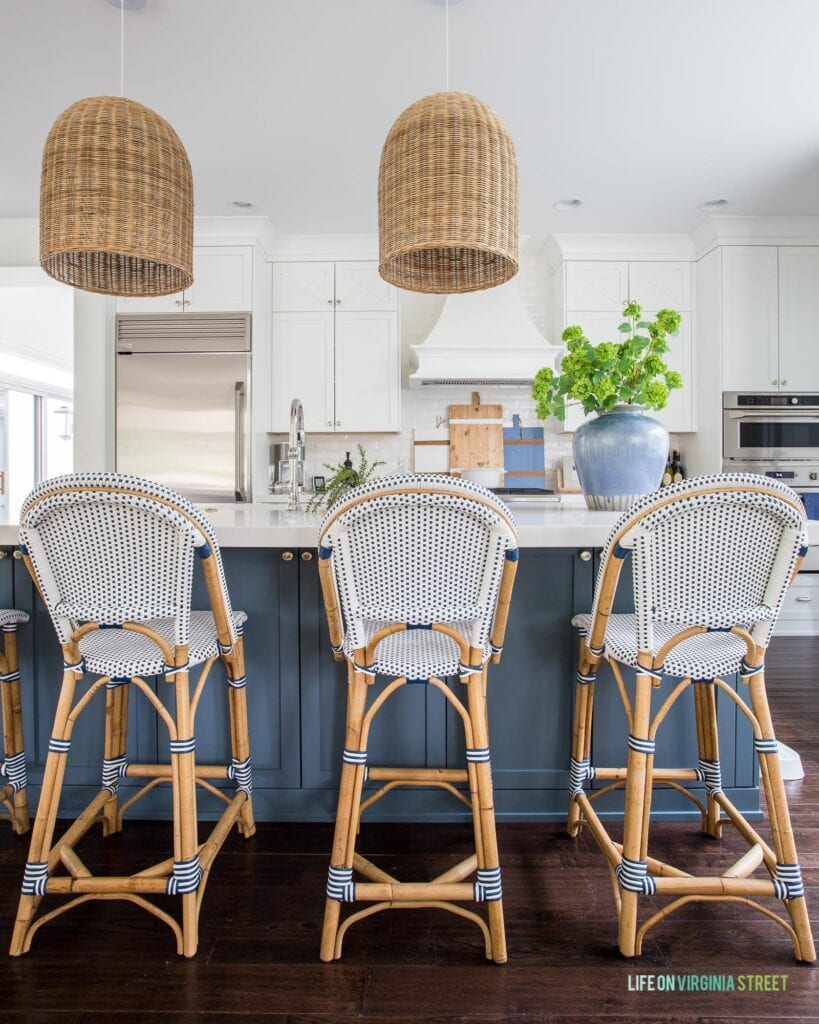 A coastal kitchen with white cabinets, blue island, Riviera counter stools, basket pendant lights, and a blue vase filled with viburnum flowers.