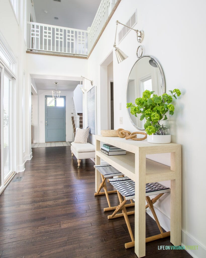 Entryway hallway with a raffia console table, striped stools, round mirror, and blue interior front door.
