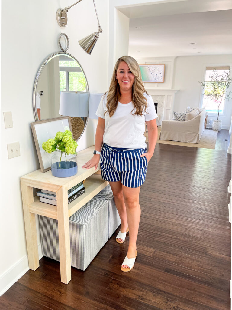 Walmart fashion finds for summer including blue and white striped shorts, a u-neck t shirt, and white slide sandals.