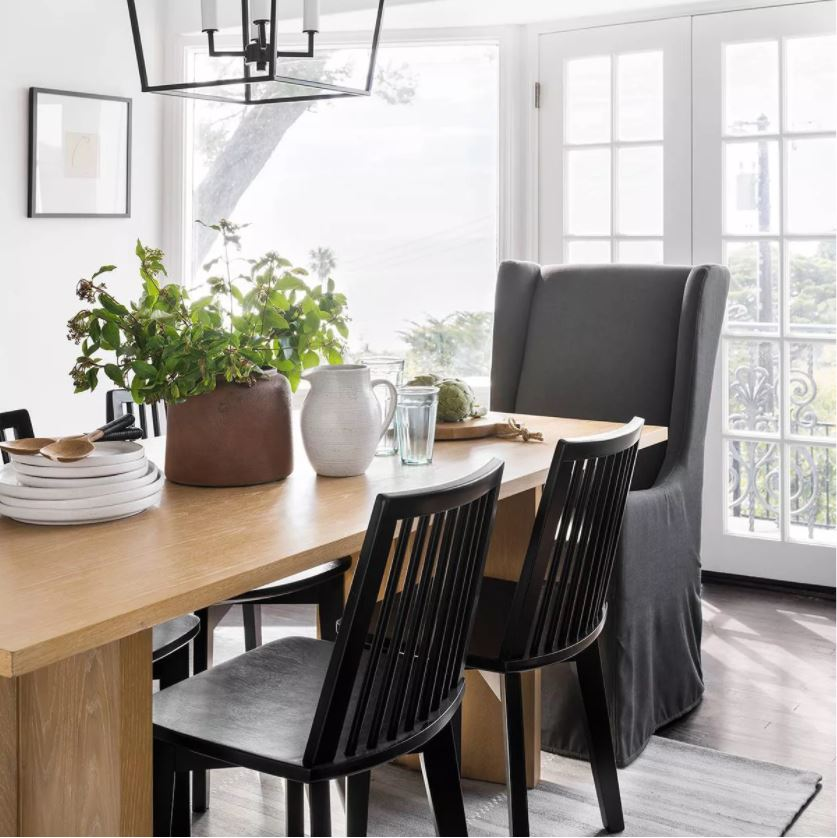 A dining room decorated with items from the 2021 Studio McGee fall collection at Target! I love the dark gray upholstered chair, black wood chairs, brown rustic pot, and black lantern pendant light.