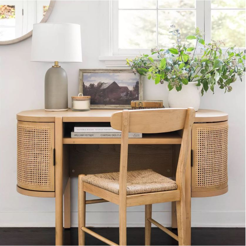 Affordable home office furniture from the Studio McGee fall collection at Target! Includes a cane desk, woven chair, ceramic lamp, framed art and a white textured pot with greenery.