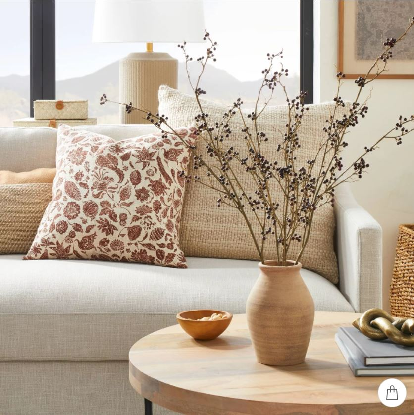 A living room decorated with neutral and floral pillows, a ceramic vase with faux berry stems, a round coffee table, fluted lamp and vintage textile art.