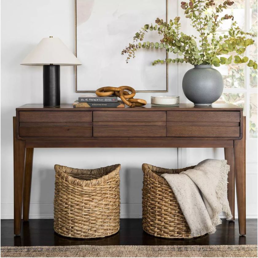 Studio McGee x Target Fall 2021 Collection Favorites including a dark wood console table, a black column lamp, gray round vase, woven baskets, oversized abstract art and a teak chain link decor piece.