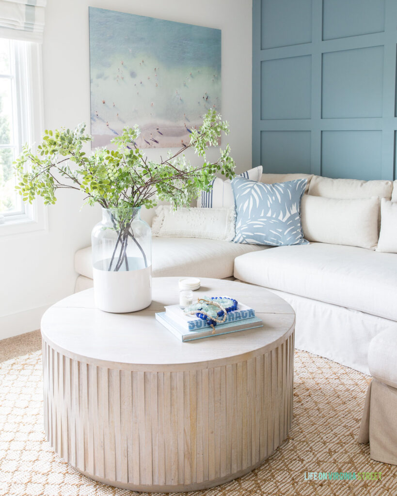 Sharing my favorite traditional coastal coffee tables like this gray washed fluted coffee table decorated in a blue and white den with beach art. Includes many more styles and options.