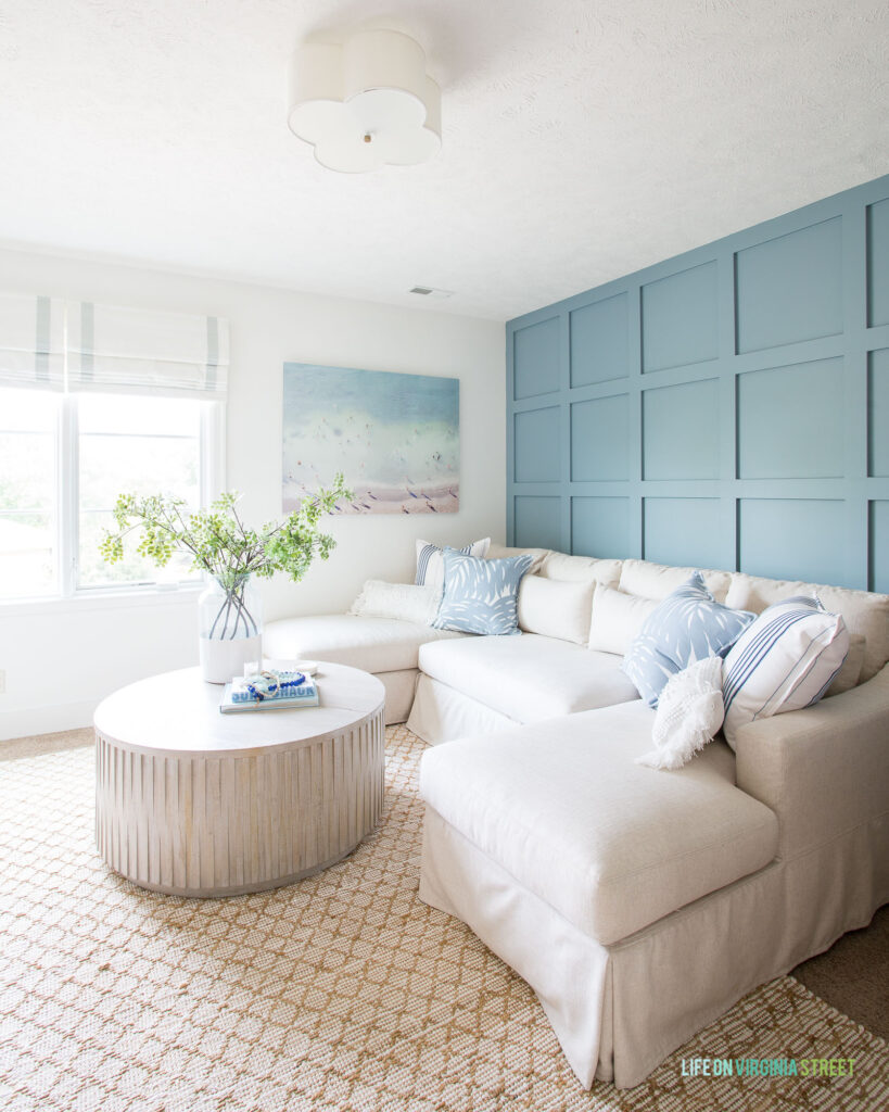 A cozy TV room with blue board and batten grid wall, linen sectional, fluted coffee table, jute rug, beach art, and roman shades.