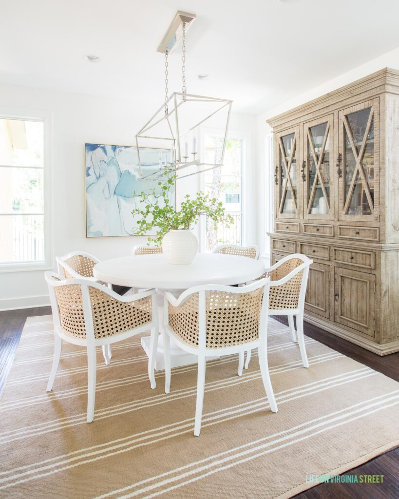 A coastal style dining room with white walls, a white concrete dining table, cane dining chairs, a linear chandelier, wood hutch, striped rug, and blue abstract art.