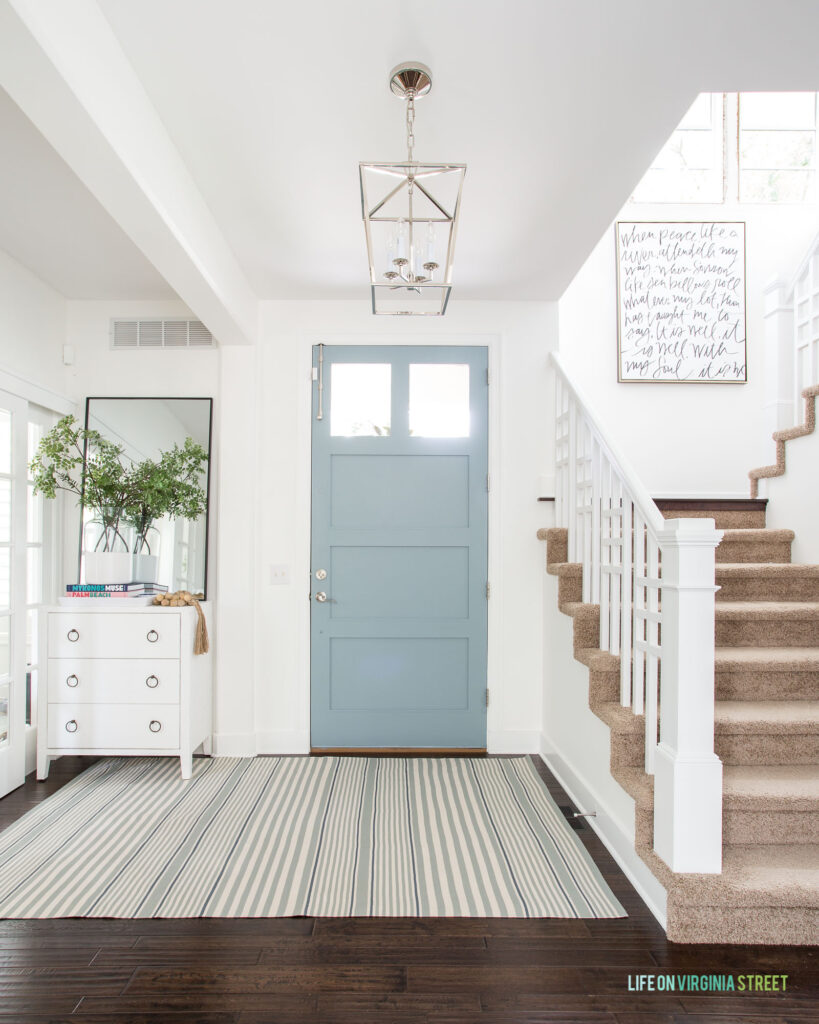 A light and bright entryway with Water's Edge painted front door, striped rug, faux greenery, tall mirror, and lantern pendant light in this 2021 Summer home tour.