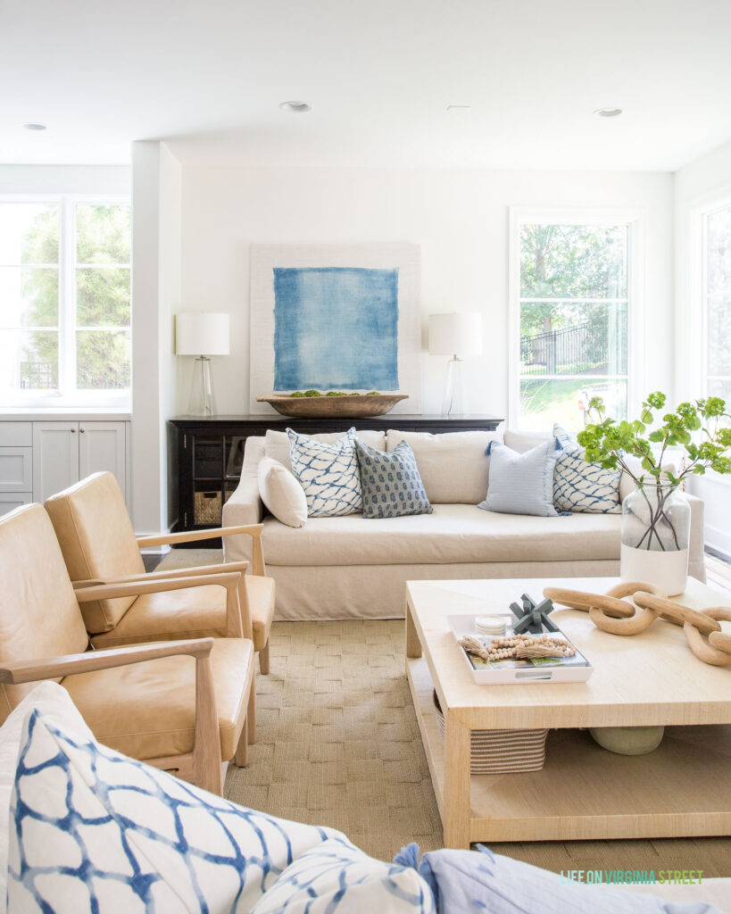 A summer living room featuring an oversized blue and white abstract art piece, leather chairs, linen sofa, raffia coffee table and blue and white pillows in a 2021 summer home tour.