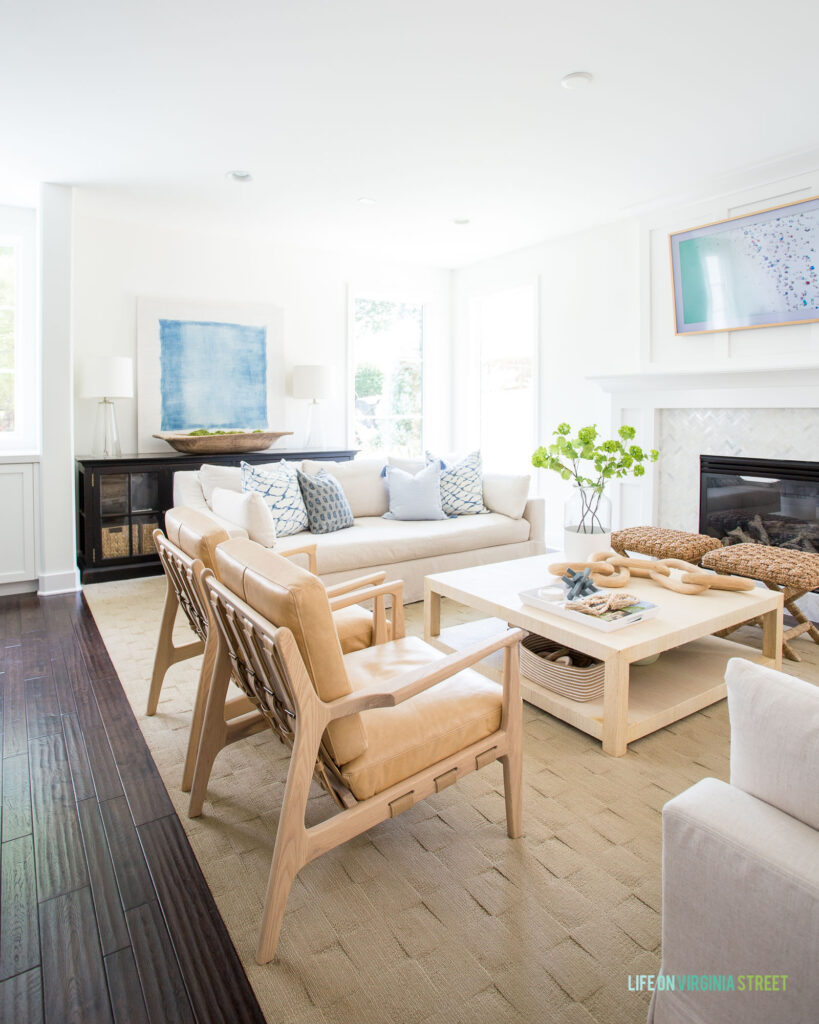 A living room decorated for summer with linen sofas, leather buckle-back chairs, a raffia coffee table, blue and white pillows, and a large watercolor abstract artwork.