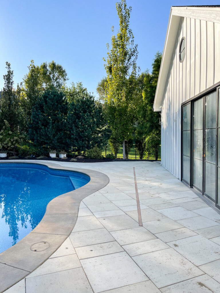 An in-ground channel drain installed between a swimming pool and a house.
